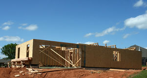 New House Frame. In process of construction, bright sunshine and blue sky Royalty Free Stock Photos