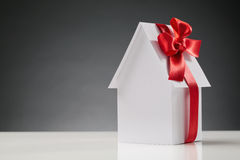 New House or Home Concept. A new white paper house with a red ribbon on it - buying a new home concept Royalty Free Stock Photography