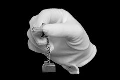 New house key. A hand in a white glove holding the key to a new house, isolated on black Stock Images