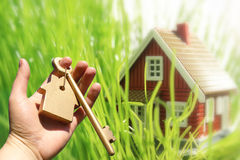 New house owner. Hand holding golden key. New house on the background royalty free stock photography