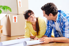 New house plans. Couple looking over plans to new house together lying on wooden floor Royalty Free Stock Photos
