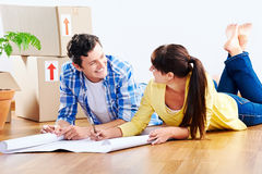 New house plans. Couple looking over plans to new house together lying on wooden floor Royalty Free Stock Photo