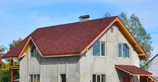 New House Roof Covered with Bitumin Tiles. Asphalt Shingles Roofing Advantages. Stock Images