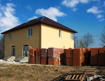 New house with stacks of bricks for the construction Stock Image