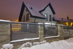 New house with stone fence at snowy night. Stonework winter outdoor nobody architecture dusk twilight dark home gray concrete wall construction material facade stock images