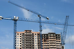 New house and three tall crane. Three blue construction crane on the background of the new building Royalty Free Stock Photo