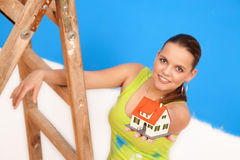 New house for you. Woman worker at the ladder with miniature house Royalty Free Stock Photography