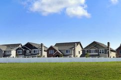 New houses. Row of newly built single-family houses behind a white fence. Lots of blue sky and green grass Stock Photography