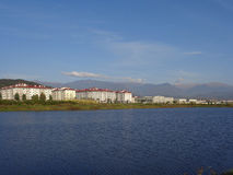 New houses on the shore of the pond. New apartment buildings near the pond, mountains on horizon, Adler, Russia Stock Photography