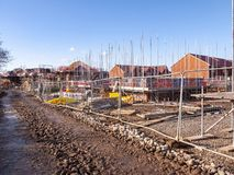 New houses under construction in Cheshire UK. New homes in scaffolding protected by safety fence in Cheshire England United Kingdom Europe royalty free stock images