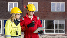 New Housing Development. Foreman and real estate development manager going over an electronic checklist during the delivery and completion of a new housing Royalty Free Stock Photography