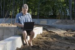 New housing starts man with laptop. At a construction site Royalty Free Stock Images