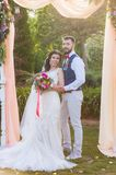 Full-length portait of just married couple. New husband and wife posing under textile arch at their wedding ceremony in the park with pink accessories. Look at Royalty Free Stock Photo