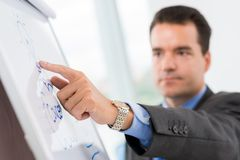 New idea. Close-up of businessman pointing at the bulb on the flipchart as a symbol of new idea Stock Photo