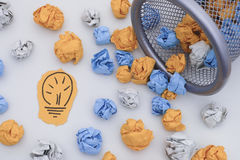 New Idea. Colorful crumpled paper balls rolling out of a trash c. An. Close up. Concept image Stock Images