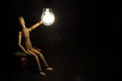 Bulb and wooden doll. New idea concept. The wooden man isolated on black background. The manikin sitting on jewelry box in a darkness and shows up by hand on a Royalty Free Stock Photo