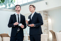 A new idea. Two other businessman drinking coffee and talking to Stock Photography