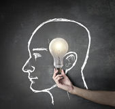New ideas. Lightning bulb in a drawed face Stock Photos