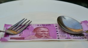New Indian currency notes of 2000 rupees. A new Indian currency note of 2000 rupees on white dish at restaurant Stock Image