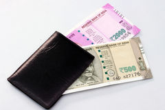 New Indian currency of 2000 and 500 rupee notes into the money purse. New Indian currency of 2000 and 500 rupee notes into the money purse on white background royalty free stock photography