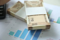 New Indian Currency Rupees from pack with chart paper. Isolated on wooden background stock image