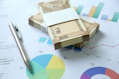 New Indian Currency Rupees from pack with chart paper and pen. Isolated on wooden background stock photography