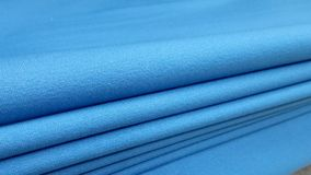 New industrial blue roll, blue background. Concept: material, fabric, manufacture, garment factory, new samples of fabrics. Royalty Free Stock Photos