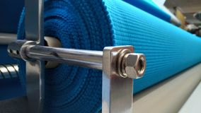New industrial blue roll, blue background. Concept: material, fabric, manufacture, garment factory, new samples of fabrics. stock image