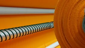 New industrial orange roll, orange background. Concept: material, fabric, manufacture, garment factory, new samples of fabrics. stock image