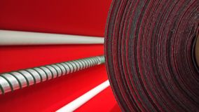 New industrial red roll, red background. Concept: material, fabric, manufacture, garment factory, new samples of fabrics. stock image