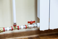 New installed central heating radiator with valve. On pipe royalty free stock image