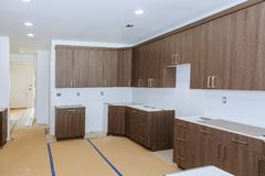 New installed wood kitchen cabinets with modern decorative stainless steel. New installed custom wood kitchen cabinets with modern decorative stainless steel stock image