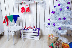 New interior corner. With white tree, purple baubles and gifts under the Christmas tree Royalty Free Stock Photography