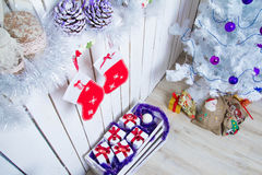 New interior corner. With white tree, purple baubles and gifts under the Christmas tree Royalty Free Stock Photos