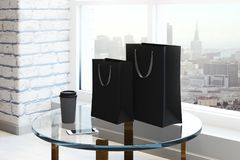 New interior with shopping bag. Empty shopping bag, coffee cup and smartphone placed on glass table in new brick interior with city view and daylight. Mock up Stock Photos
