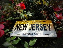 New Jersey, The Garden State License Plate Laying In A Garden Of Flowers. New Jersey license plate displayed in a flower garden in New Jersey stock photo