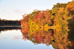 New Jersey lake and autumn foliage. Foliage, autumn, colors, still, water, reflection, landscape New Jersey, blue, sky, clouds, sunset, red, yellow, lake Stock Photo