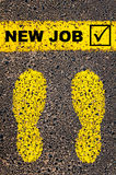 New Job and check mark sign. Conceptual image. Conceptual image with yellow paint footsteps on the road in front of horizontal line over asphalt stone background Stock Photo