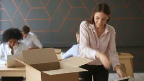 New job concept, young woman unpacking box on office desk. First day at new job concept, young happy woman unpacking box with her belongings standing near office
