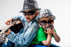 New kids on the block playing loud rock. Two little children playing and singing some music pretending to be blues or rock stars Royalty Free Stock Photos