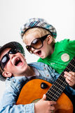 New kids on the block playing loud rock. Two little children playing and singing some music pretending to be blues or rock stars Stock Images