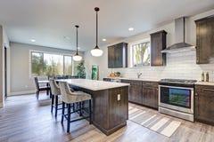 New kitchen boasts dark wood cabinets, large island stock images