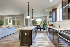 New kitchen boasts dark wood cabinets, large island. New kitchen boasts dark wood cabinets, white backsplash subway tile and over sized island with white and royalty free stock photos