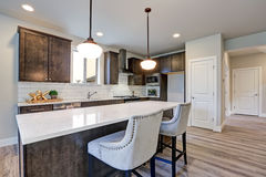 New kitchen boasts dark wood cabinets, large island. New kitchen boasts dark wood cabinets, white backsplash subway tile and over sized island with white and royalty free stock image