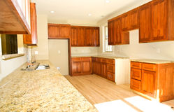 New Kitchen Cabinets/Installed. Maple wood kitchen cabinets and granite counter tops recently installed in a new house. Could depict a refurbished kitchen, also royalty free stock images