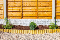 New landscaped wood chip garden border. With small wooden fence edging and plants.  Concrete posts and gravel boards and timber fencing Stock Photo