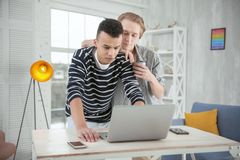 Pensive gay couple estimating laptop. New laptop. Nice concentrated gay couple standing while looking down and using laptop Stock Photos