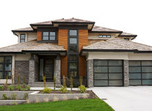 New Large Custom Home Exterior. Exterior view of a new custom home with a shake roof and custom glass garage doors Royalty Free Stock Images