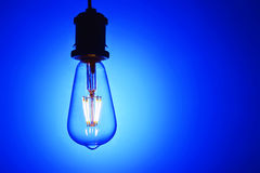 New led light bulb over blue background. New type led lamp bulb over blue background.three generations of light bulb such as regular incandescent lamp bulb royalty free stock image