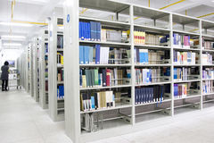 New library. With lots of shelves and books,one girl read books at corner Stock Photos